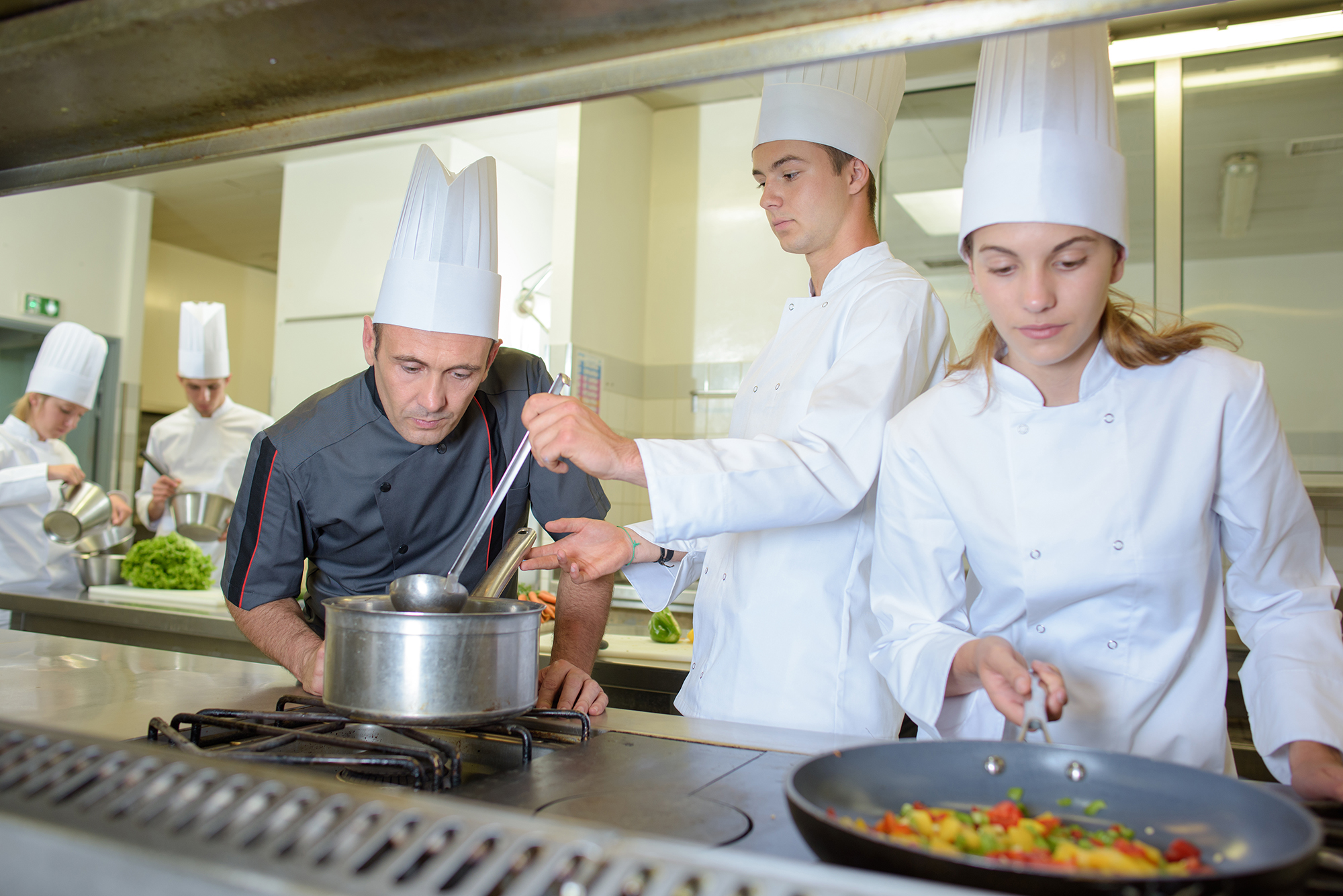 Chef observing trainee cooks
